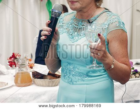 Happy Mother In Law With Champagne In Glass Holding Microphone And Pronouncing Toast At Wedding Rece