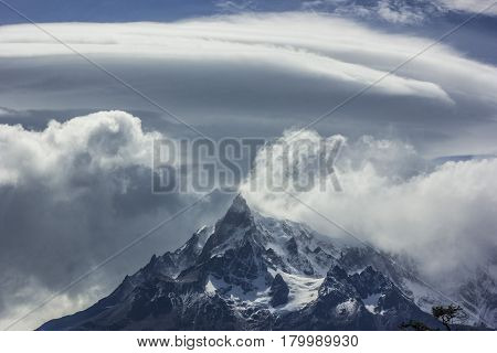 mountains of patagonia in haze at daylight with windy clouds and blue sky