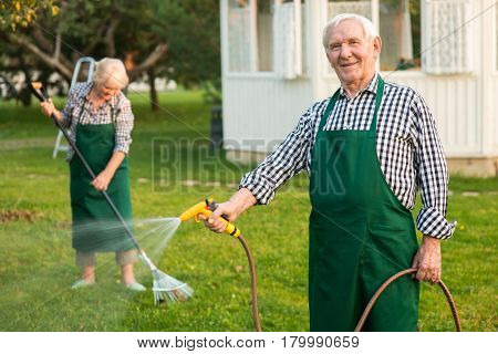 Man with garden hose smiling. Senior male in apron outdoors. Find jobs in gardening.
