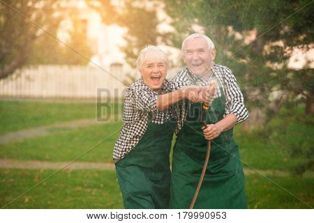 Senior couple having fun. Gardeners and water hose.