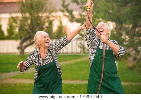 People having fun, garden hose. Cheerful old couple outdoors.