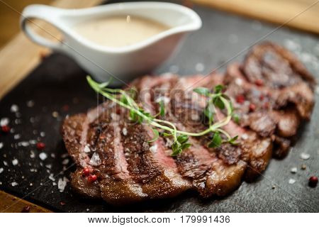 Sliced steak Picanya with sauce served on s stone board