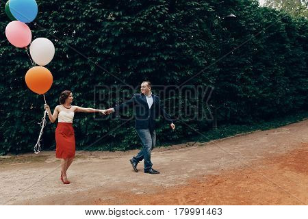 Cheerful Groom In Stylish Clothes Leading Happy Bride By Her Hand In A Park, Newlywed Couple On A Wa