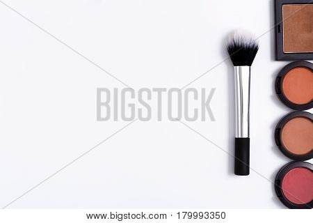 Makeup cosmetics, brush and blushes on white background. Top view, flat lay with copy space. Beauty tools palettes collection