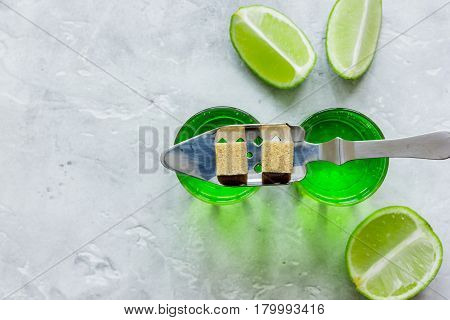 absinthe shots with fresh green lime slices and sugar cubes on stone bar table background top view mock-up