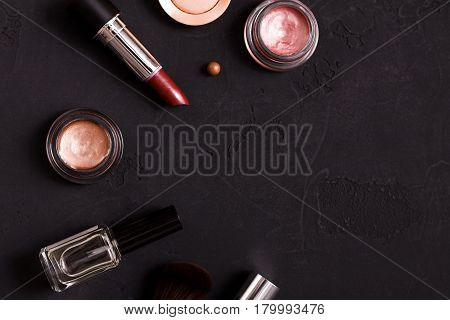 Makeup cosmetics, lipstick, gloss and other essentials frame on black background. Top view, flat lay with copy space. Beauty tools collection