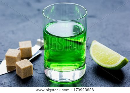 green absinthe with sugar cubes in spoon on dark table background