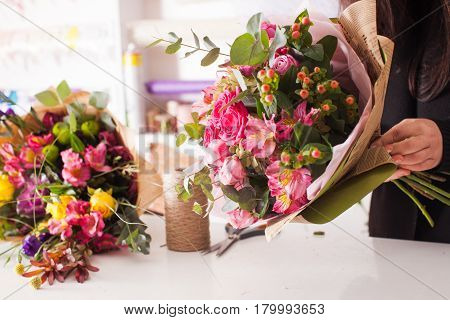 Florist making fashion bouquet of pink flowers