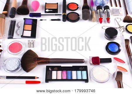 Makeup cosmetics, brushes and other essentials frame on white background. Top view, flat lay with copy space. Beauty tools collection, lipstick, eyeshadow, mascara, foundation and more