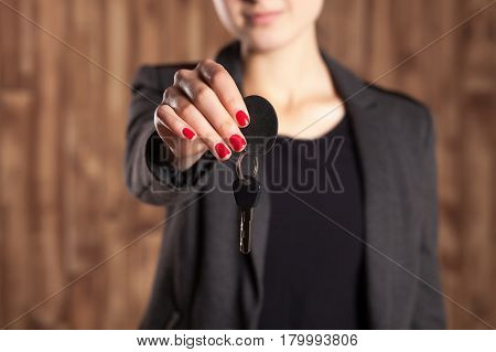 Woman with red lacquer on nails holds her car keys on brown background