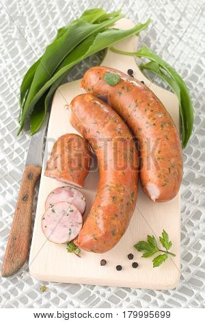 Sausages with ramsons leaves on a wooden cutting board.