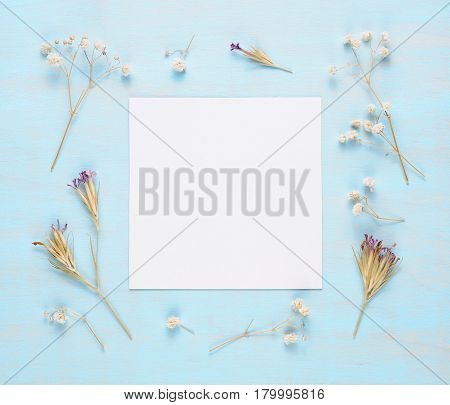 Blank greeting card and dry flowers on blue wooden background