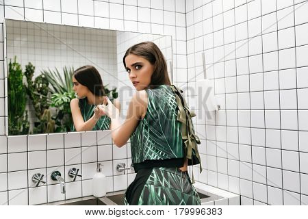 Serious young woman standing and touching mirror in water closet