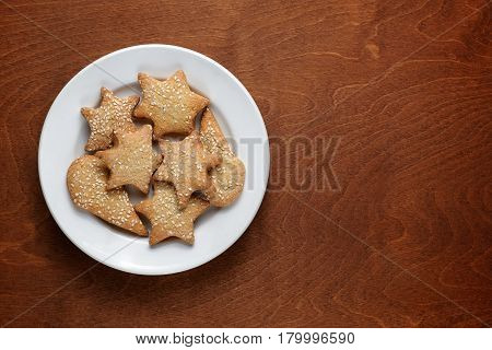 Homemade cookies with sesame in plate on wooden table