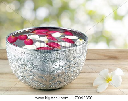 flower petals floating on surface of water in silver bowl on wooden table floor with bokeh background from space between green leaf, used for decorative Asian style or in Songkran festival