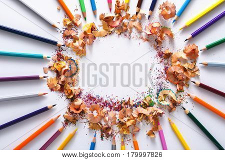 Drawing tools, lot of colorful pencils in circle with sawdust and shavings on white isolated background, copy space, flat lay