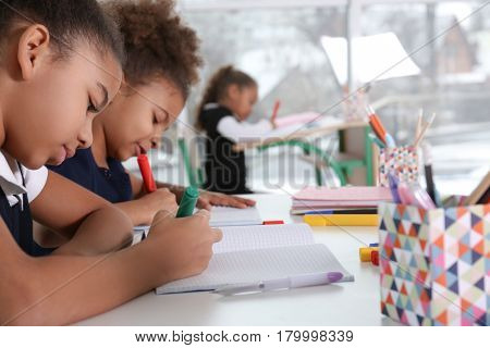Cute African-American girls drawing at lesson