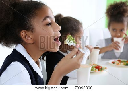 Cute African-American girls in dinning room at school