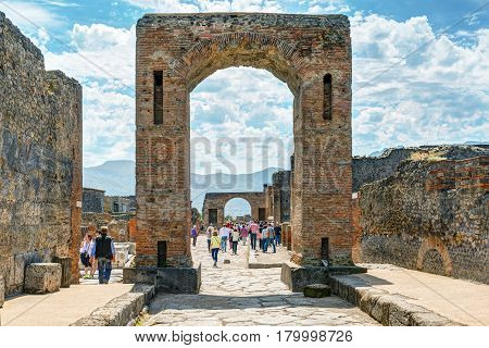 POMPEII, ITALY - MAY 13, 2014: Tourists visit the ruins of the city. Pompeii is an ancient Roman city died from the eruption of Mount Vesuvius in 79 AD.