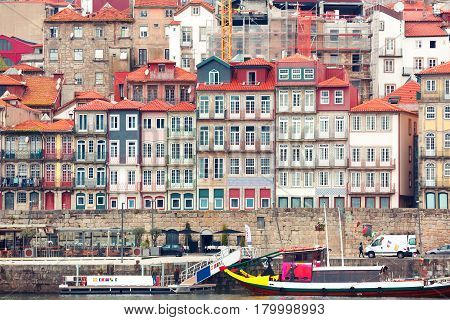 Traditional multicolored quaint houses in Ribeira - the old, vintage and touristic district of Porto and the promenade Douro river, Portugal