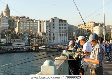 ISTANBUL - MAY 26: Fishermen are on the Galata Bridge on may 26, 2013 in Istanbul, Turkey. The Galata Bridge is one of the main attractions of Istanbul.