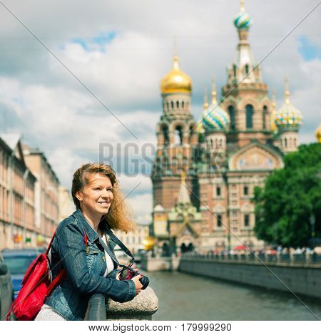 Young female tourist near the Church of Savior on Spilled Blood (Cathedral of the Resurrection of Christ) in Saint Petersburg, Russia