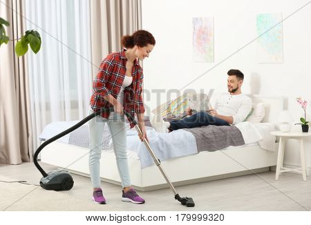 Man reading newspaper on bed while woman hoovering floor at home