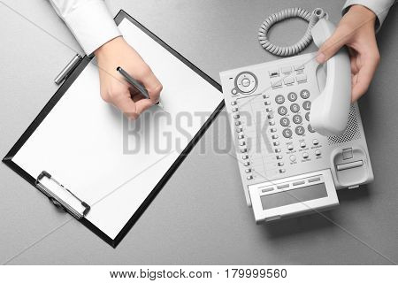 Hands of man picking up telephone receiver while working in office