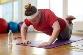 Portrait of young obese woman working out on yoga mat in sunlit fitness studio: performing knee push up exercise with effort to lose weight poster