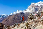 View of Himalaya Mountains and Nepalese professional Guide in blue Jacket staying on rocky Slope with red Backpack poster
