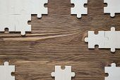 Incomplete wooden puzzles on brown wooden desk top view flat lay. Frame with puzzle. The concept of logical thinking business conundrum. Business concept with jigsaw puzzle on wooden background. poster