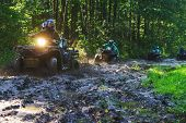 Summer Activities for adults - a trip on quad bikes on the road. Man on ATV in the mud on the road to participate in the race over rough terrain in the forest on a hot summer day. poster