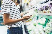 Young woman shopping healthy food in supermarket blur background. Female hands buy products cabagge using smartphone in store. Hipster at grocery using smartphone. Person comparing price of produce poster