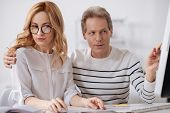 Sexual harassment in business office. Cheerful flirting mature businessman sitting in the office and working on the project while flirting and touching young secretary shoulder poster