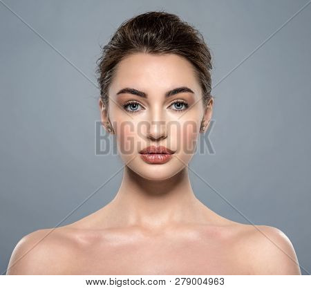 Portrait of beautiful young brunette woman with clean face. Beautiful face of  a caucasian model with clean fresh skin. Closeuo front female portrait.