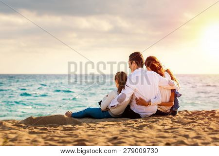 Close Up Of Young Family Sitting Together In Late Afternoon Sun On Beach.foursome Giving Back Lookin