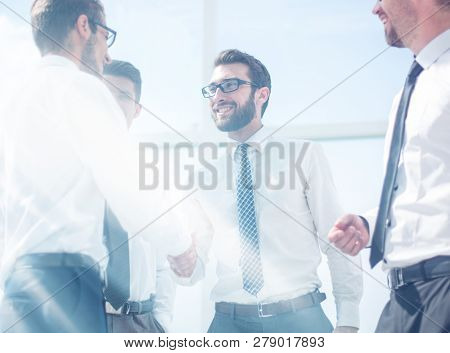 business people shaking hands while standing in the office