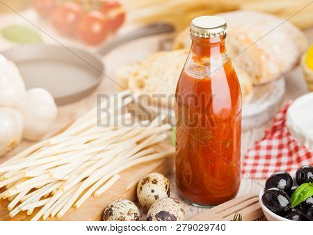 Homemade Spaghetti Pasta With Quail Eggs With Bottle Of Tomato Sauce And Cheese On Wooden Background