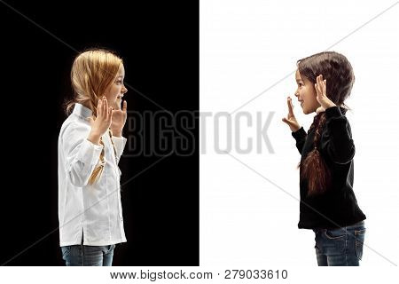 The Profile Portrait Of Two Happy Girls On A White And Black Studio Background. Human Emotions Conce
