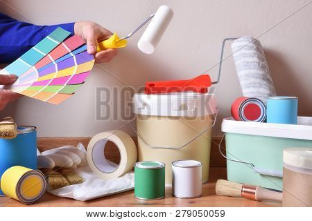Painting Tools For Home On Parquet With White Wall Background And Painter Choosing Colors On A Color