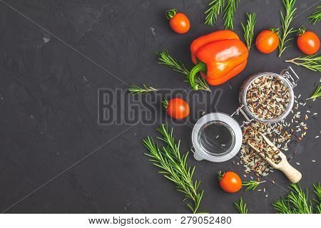 Mix Rise With Vegetables And Herb On Black Concrete Surface