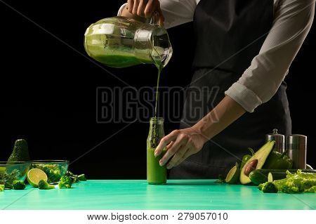 A Chef On A Black Background Makes Cooking A Green Detox Smoothie And Pours It Into Bottles. Healthy