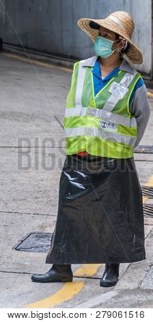 Hong Kong, China  - May 12, 2010: Female Traffic Warden At Parking Exit With Fluorescent Yellow Jack