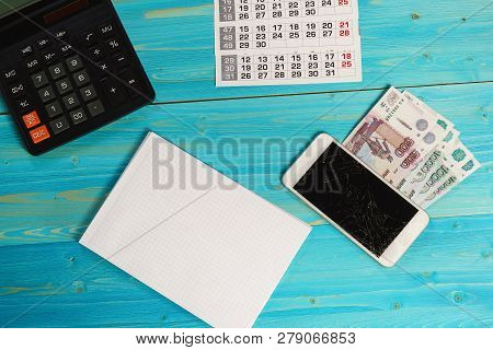 Calendar, Clean Notebook, Broken Smartphone And Russian Money On The Blue Table. Unforeseen Expenses