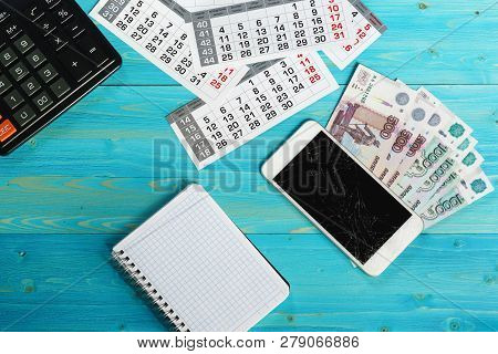 Calendar, Broken Smartphone And Russian Money On A Blue Wooden Table. Unforeseen Expenses Have Disru