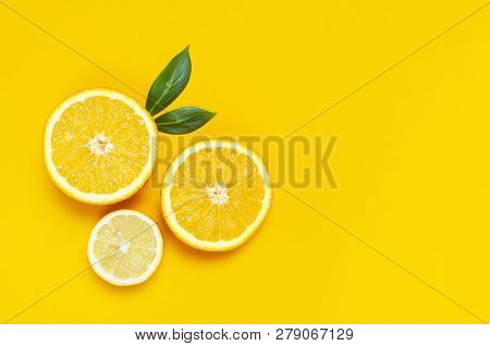 Ripe Juicy Lemons, Orange And Green Leaves On Bright Yellow Background. Lemon Fruit, Citrus Minimal