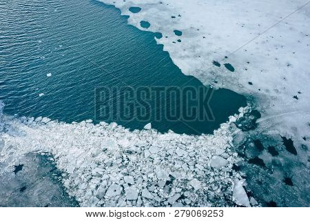 Glacier Lagoon With Icebergs From Above. Aerial View. Cracked Ice From Drone View. Background Textur
