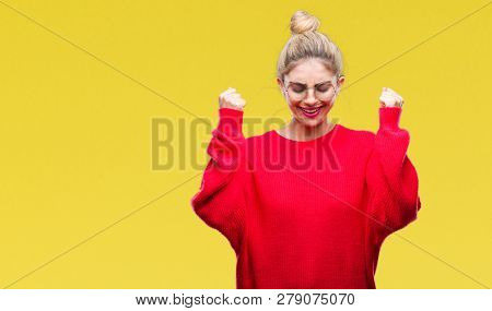 Young beautiful blonde woman wearing red sweater and glasses over isolated background excited for success with arms raised celebrating victory smiling. Winner concept.