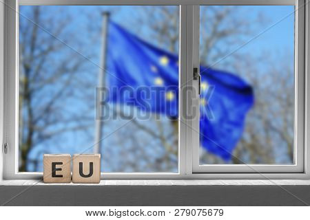 Eu Sign In A Window With The European Union Flag Outside Waving In The Wind