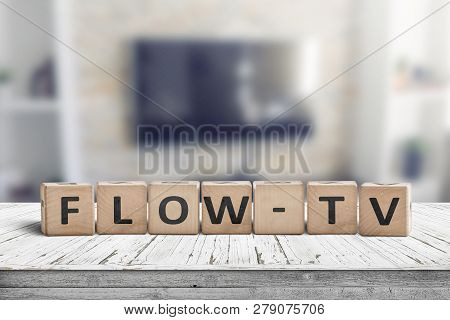 Flow-tv Sign On A Wooden Table In A Living Room With A Tv On The Wall